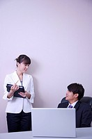 Young man and woman talking in office and smiling at each other (thumbnail)