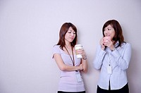 Two women drinking coffee at coffee break and smiling