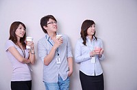 Three colleagues holding drinks and looking up with smile together