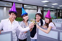 Four colleagues wearing headwear and toasting with smile