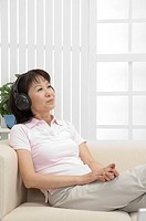 Wife, Woman lying on sofa and listening music with smile