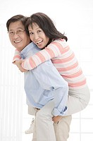 Couple, Wife on husband's back and looking at the camera with smile