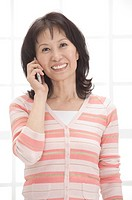 Woman holding mobile phone and smiling at the camera