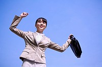 Young businesswoman holding briefcase with arms outstretched and looking away with smile