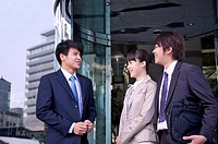 Three colleagues standing and talking together with smile