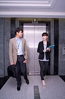 Young man and woman walking before elevator and talking together
