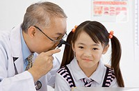 Doctor checking little girl's ear with medical equipment (thumbnail)