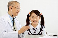 Doctor using stethoscope to examine little girl