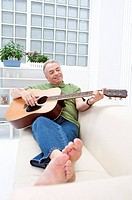 Domestic Life, a senior man lying on sofa and playing guitar