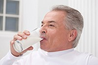 Domestic Life, a senior man drinking a glass of milk and looking away