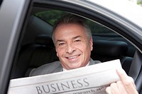 Senior businessman sitting in the car, reading newspaper and smiling at the camera