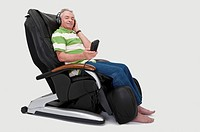 Domestic Life, a senior man sitting on the massaging chair and listening to music