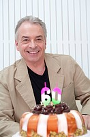 Domestic Life, a senior man sitting with birthday cake and smiling happily