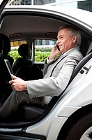 Senior businessman sitting in the car, using laptop and mobile phone