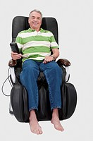 Domestic Life, a senior man sitting on the massaging chair and smiling