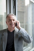 Senior businessman using mobile phone and looking at the camera with smile