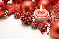 A lit candle and Christmas Ornaments