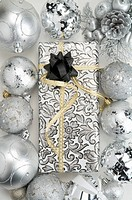 Christmas baubles around a packed gift with ribbon
