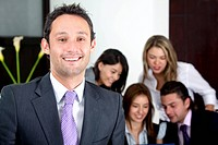 business man smiling leading a team in an office