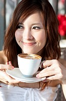 Coffee Break, Taste of Life, Young woman holding a cup of coffee and looking away with smile