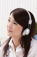 Close_up of woman listening music and looking away with smile