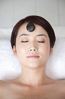 Beauty Treatment, Woman lying with eyes closed and a pebble on face