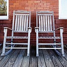 Two old rocking chairs on porch.