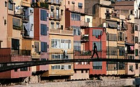 Man walking across a pedestrian bridge across the River Onyar, in the heart of Girona, backed by a colourful array of multistoried houses