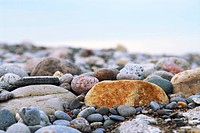 Background of colourful beach pebbles of different shapes and water