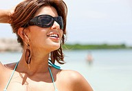 beach woman portrait in a bikini wearing sunglasses.