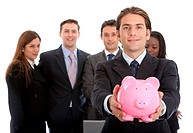 Business man showing his savings in a piggy bank with his team behind him