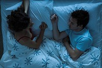 Couple lying together in bed, woman watching man sleeping
