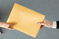 Handing colleague large brown envelope (thumbnail)
