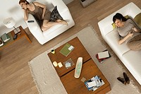 Women relaxing in living room, one listening to MP3 player
