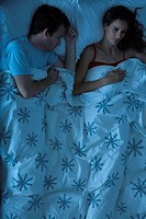 Couple lying together in bed, woman restlessly awake