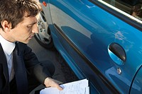 Insurance adjuster examining damage to car exterior (thumbnail)