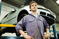 Mechanic in auto repair shop, car on hydraulic lift in background