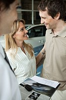 Couple at car dealership preparing to buy new car