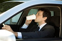 Man drinking coffee while driving car