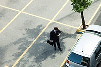 Businessman checking time as he walks to parked car