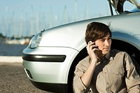 Man having car trouble, making phone call with cell phone