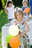 Girl wearing tiara and holding balloons at outdoor party