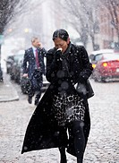 Asian woman walking in snow and wiping nose