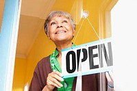 African American business owner hanging open sign on door