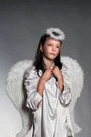 studio portrait of an eleven years old girl dressed as angel