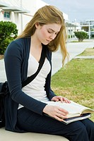 Female college student sitting on bench reading book on campus