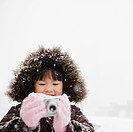 Chinese girl in snow using digital camera