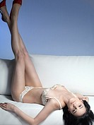 Young beautiful woman in lingerie lying on a sofa