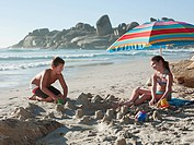 Boy and girl making sandcastles on beach (thumbnail)