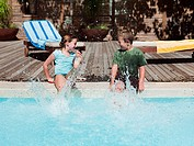 Boy and girl splashing in swimming pool
